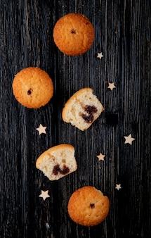 Bovenaanzicht cupcakes met chocolade met sterren op een zwarte houten achtergrond