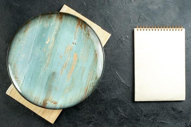 Bovenaanzicht cyaan ronde schotel beige bord notebook op zwarte tafel