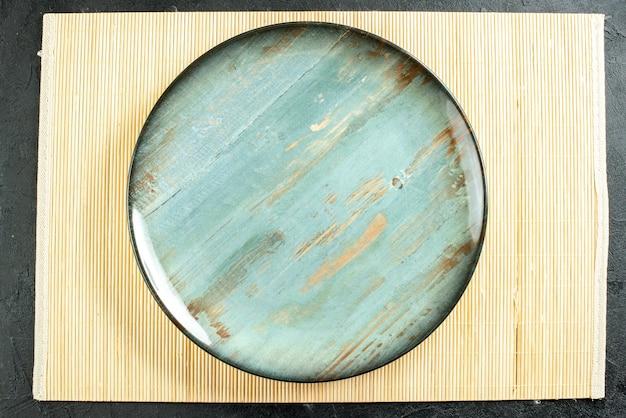 Bovenaanzicht cyaan ronde schotel beige bord op zwarte tafel
