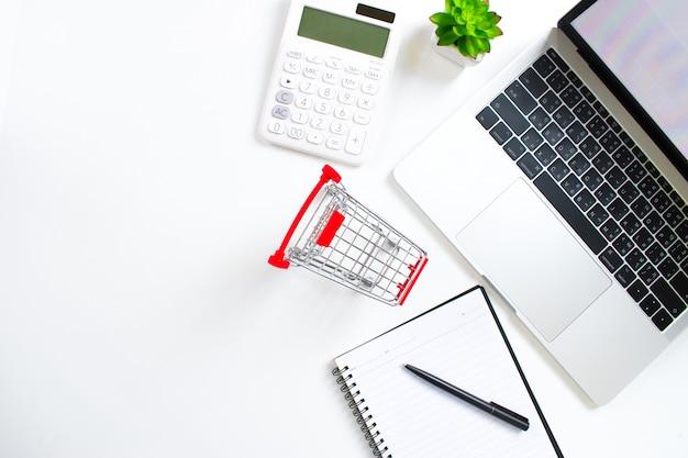 Bovenaanzicht dat bestaat uit een laptop, een computer, een winkelwagentje, een penboek en een rekenmachine