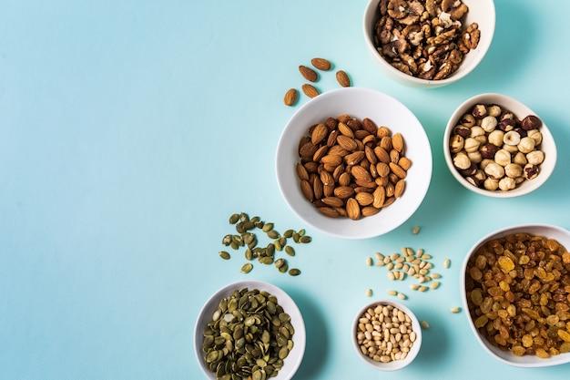 Bovenaanzicht de set van superfoods en noten in kommen op blauwe achtergrond met kopie ruimte.