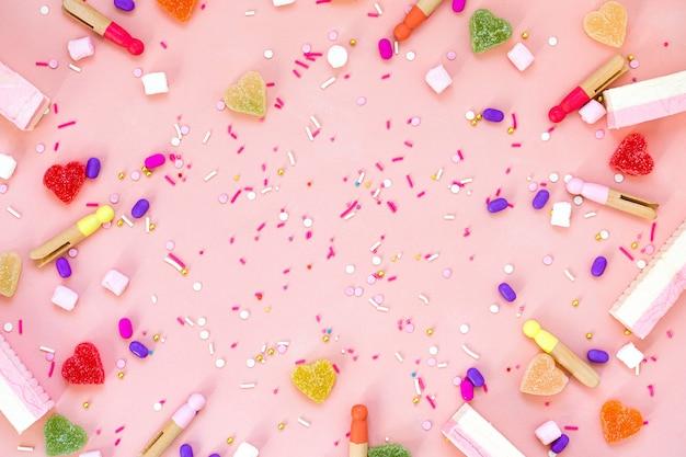 Bovenaanzicht decoratie geassorteerde kleverige snoepjes en jelly snoepjes gelukkig vakantie concept. plat lag kleurrijke snoep op mooie roze bureau. kopieer ruimte.