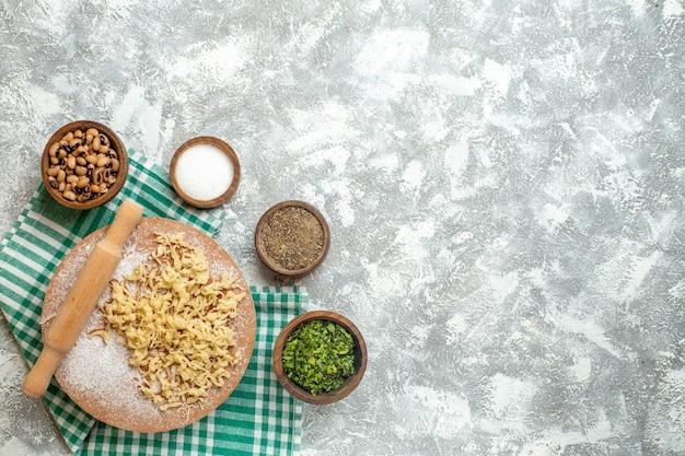Bovenaanzicht deeg en deegroller op deegbord op tafelkleed op grijze achtergrond