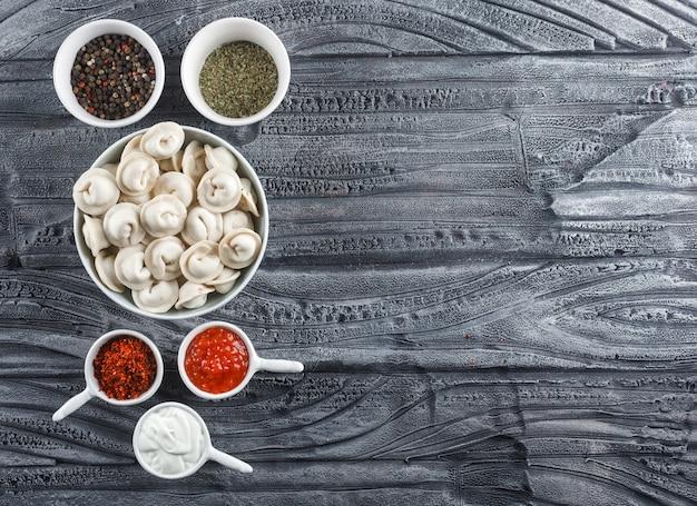 Bovenaanzicht deeg in kom met saus, kruiden op grijze houten oppervlak. horizontale ruimte voor tekst