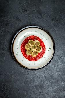 Bovenaanzicht deeg met vlees gesneden deegplakken met tomatensaus op grijze ruimte