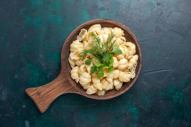 Bovenaanzicht deeg pasta met groenen binnen plaat op het donkere oppervlak gekookt