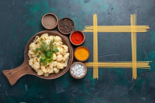 Bovenaanzicht deeg pasta met verschillende kruiden op het donkere oppervlak gekookt