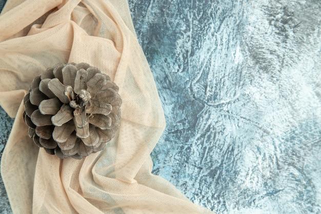 Bovenaanzicht dennenappel op beige sjaal op donkere ondergrond vrije plaats