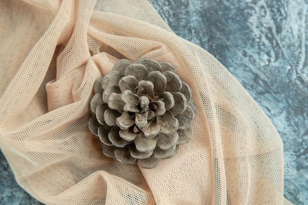 Bovenaanzicht dennenappel op beige sjaal op donkere ondergrond