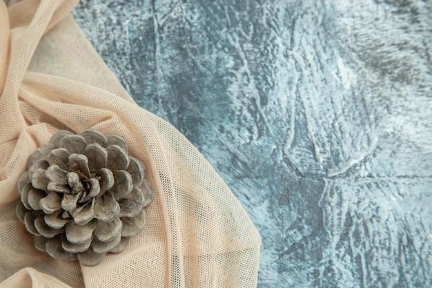 Bovenaanzicht dennenappel op beige sjaal op donkere oppervlakte vrije ruimte