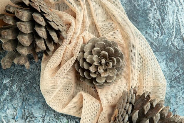Bovenaanzicht dennenappels op beige sjaal op donkere ondergrond