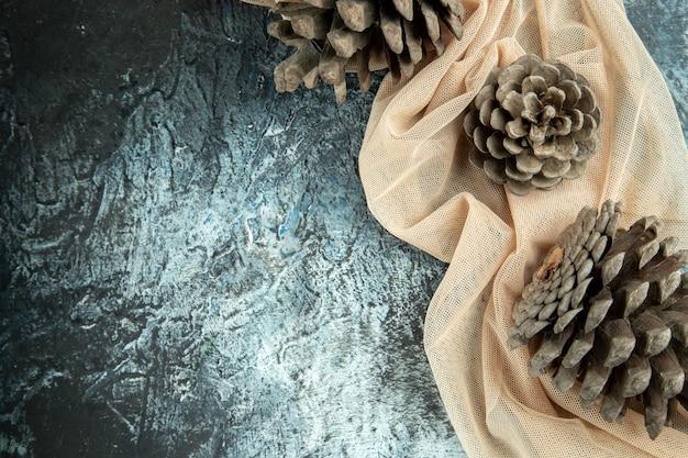 Bovenaanzicht dennenappels op beige sjaal op donkere oppervlakte kopie ruimte