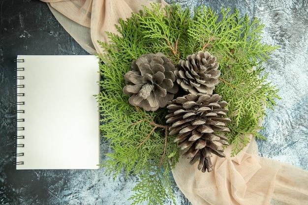 Bovenaanzicht dennenappels pijnboomtakken op beige sjaal notebook op donkere ondergrond