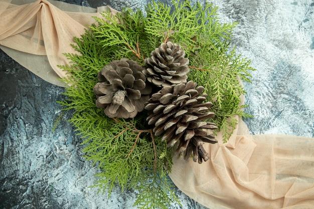 Bovenaanzicht dennenappels pijnboomtakken op beige sjaal op grijs oppervlak