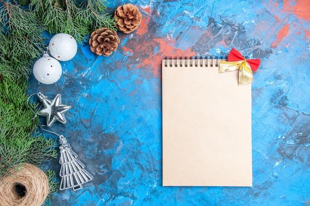 Bovenaanzicht dennenboom takken dennenappels kerstboom ballen stro draad notitieboekje met strikje op blauw-rood oppervlak