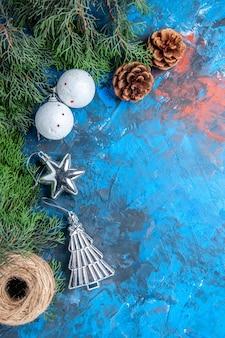 Bovenaanzicht dennenboom takken dennenappels kerstboom ballen stro draad op blauw-rood oppervlak