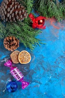 Bovenaanzicht dennenboom takken dennenappels kerstboom speelgoed gedroogde schijfjes citroen op blauw-rood oppervlak