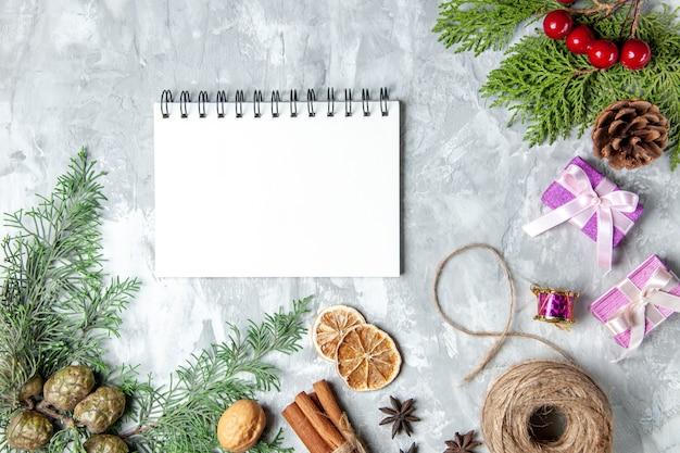 Bovenaanzicht dennenboom takken kaneelstokjes stro draad notebook anijs op grijze achtergrond gray