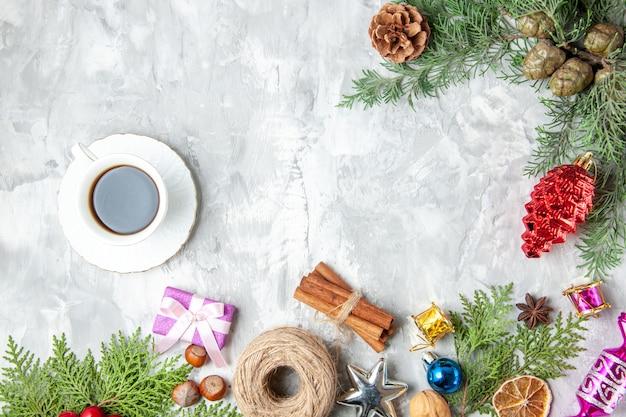 Bovenaanzicht dennenboom takken kegels kerstboom speelgoed kaneelstokjes anijs een kopje thee op grijze achtergrond