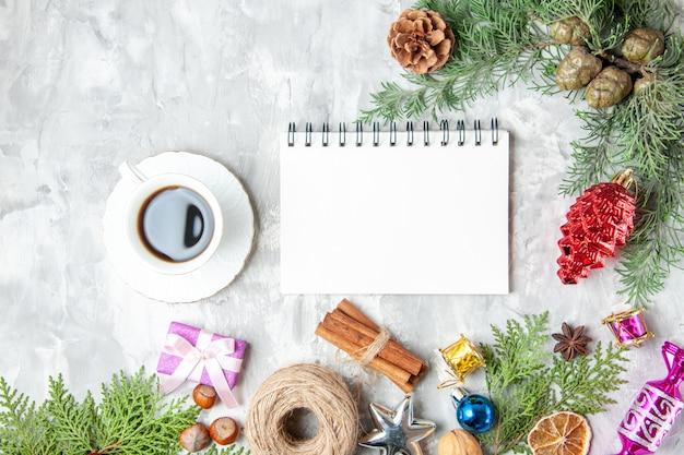 Bovenaanzicht dennenboom takken kegels kerstboom speelgoed kaneelstokjes anijs notitieboekje een kopje thee op grijze achtergrond