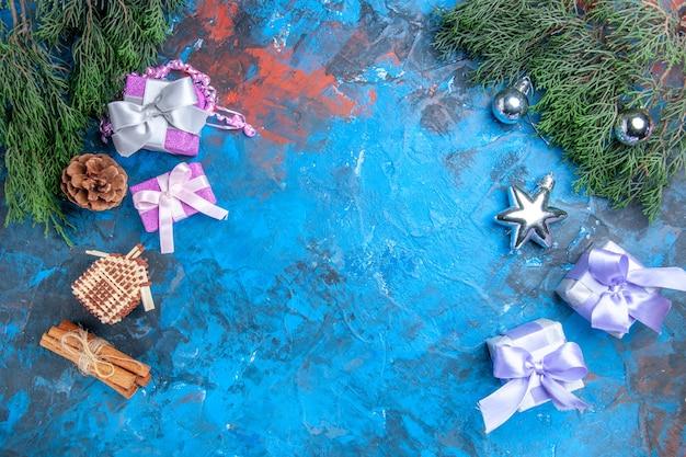 Bovenaanzicht dennenboom takken kerstboom speelgoed kerstcadeaus kaneelstokjes op blauw-rode achtergrond met kopie ruimte