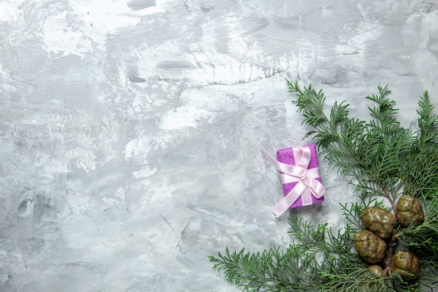Bovenaanzicht dennenboom takken klein cadeautje op grijze ondergrond