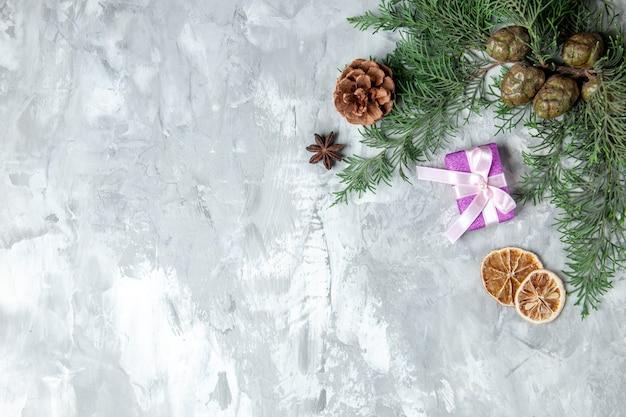 Bovenaanzicht dennenboom takken klein geschenk gedroogde schijfjes citroen op grijze achtergrond