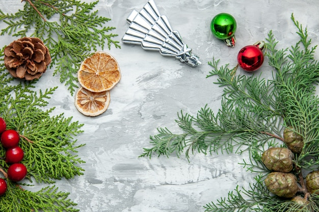 Bovenaanzicht dennenboom takken kleine geschenken kerstboom speelgoed gedroogde schijfjes citroen op grijs oppervlak