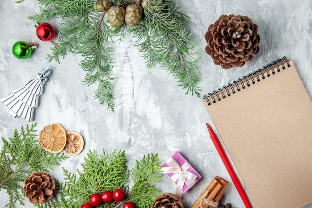 Bovenaanzicht dennenboom takken kleine geschenken kerstboom speelgoed notebook potlood op grijze achtergrond