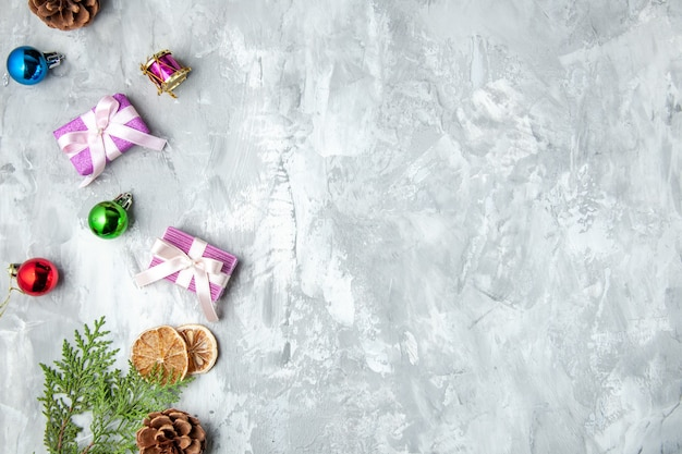 Bovenaanzicht dennenboom takken kleine geschenken kerstboom speelgoed op grijs oppervlak