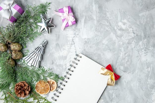 Bovenaanzicht dennenboom takken notebook dennenappels kleine geschenken gedroogde schijfjes citroen op grijs oppervlak