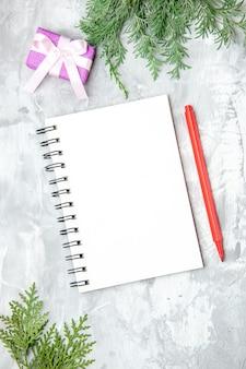 Bovenaanzicht dennenboom takken notebook potlood klein cadeautje op grijze achtergrond