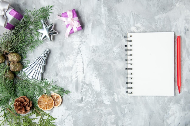 Bovenaanzicht dennenboom takken notebook rood potlood dennenappels kleine geschenken op grijs oppervlak