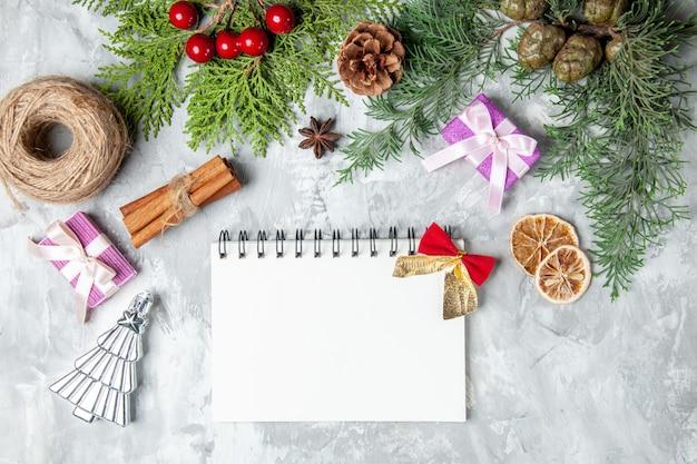 Bovenaanzicht dennenboom takken notebook stro draad kaneelstokjes kleine geschenken op grijze achtergrond