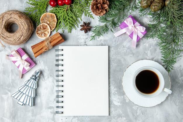 Bovenaanzicht dennenboom takken notebook stro draad kaneelstokjes kopje thee op grijze ondergrond