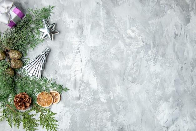 Bovenaanzicht dennenboom takken schijfjes citroen dennenappels kerstboom speelgoed op grijze ondergrond
