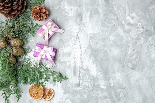 Bovenaanzicht dennenboom takken schijfjes citroen dennenappels kleine geschenken op grijs oppervlak