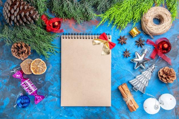 Bovenaanzicht dennenboom takken stro draad kerstboom speelgoed anijs zaden kaneelstokjes gedroogde citroen schijfjes een notitieboekje met strikje op blauw-rode achtergrond