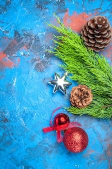 Bovenaanzicht dennenboomtak met dennenappels en kleurrijk kerstboomspeelgoed op blauw-rood oppervlak