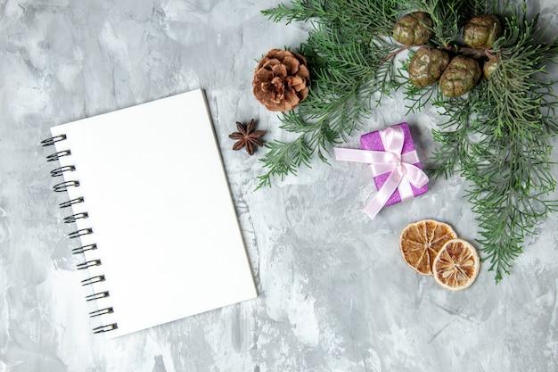 Bovenaanzicht dennenboomtakken gedroogde citroenschijfjes notebook op grijs oppervlak