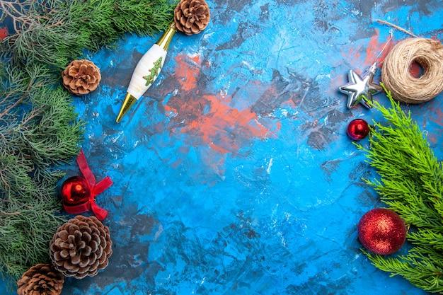 Bovenaanzicht dennenboomtakken met dennenappels stro draad op blauw-rood oppervlak