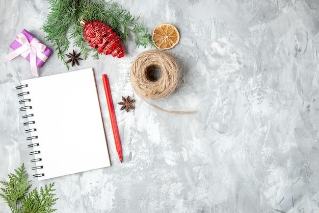 Bovenaanzicht dennenboomtakken met notitieboekje op grijze achtergrond