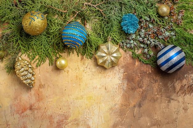 Bovenaanzicht dennentakken kerstboom ornamenten op beige achtergrond