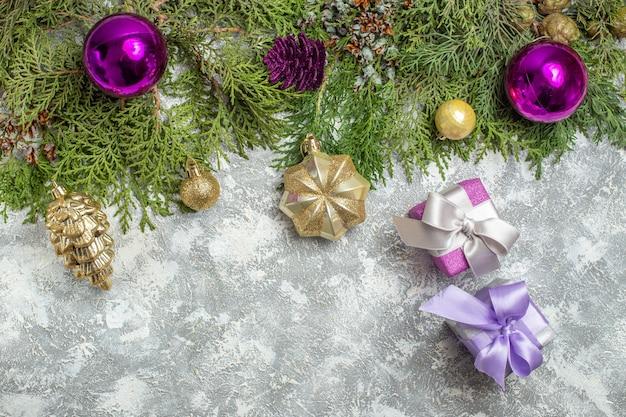 Bovenaanzicht dennentakken kerstboom ornamenten op grijze achtergrond