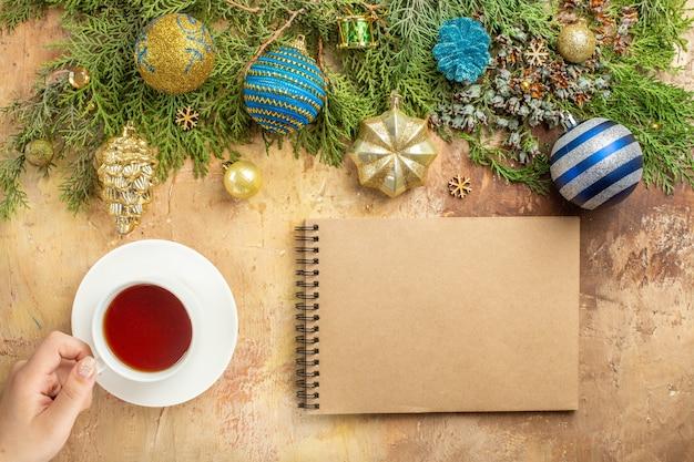Bovenaanzicht dennentakken kerstboom versieringen een kopje thee notebook op beige achtergrond