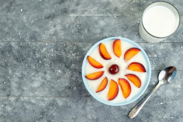 Bovenaanzicht dessert met fruit gesneden fruit in plaat samen met koude melk op blauw
