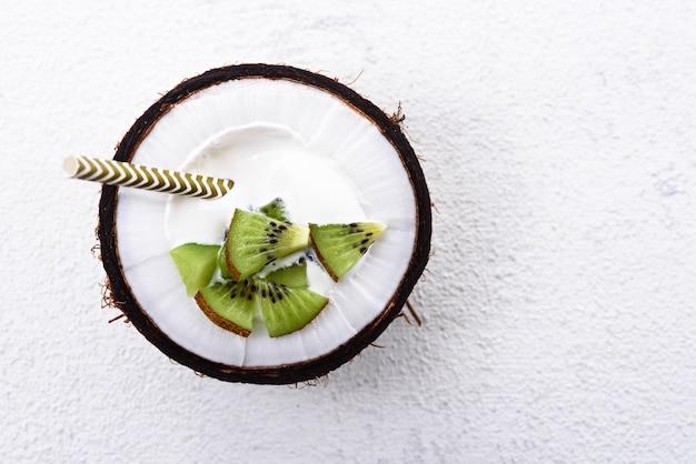 Bovenaanzicht dessert met room en kiwi in kokos kom met stro op witte achtergrond met kopie ruimte