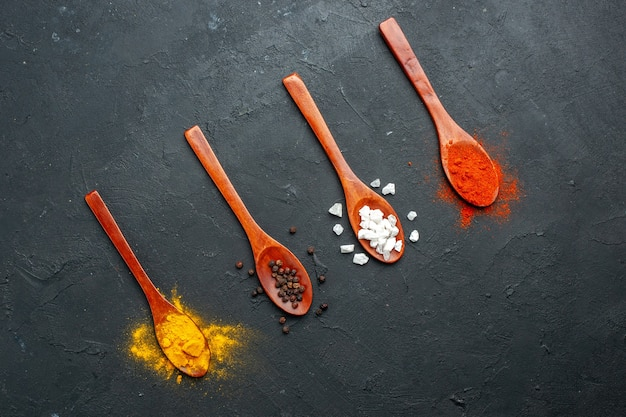 Bovenaanzicht diagonale rij houten lepels met kurkuma zwarte peper sae zout rood peperpoeder op zwarte tafel