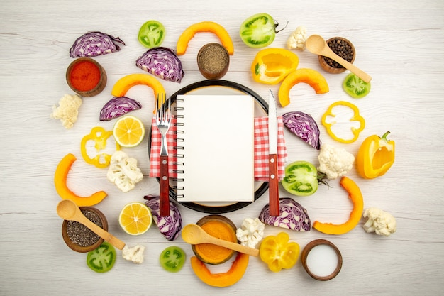 Bovenaanzicht dieet geschreven op kladblok vork en mes op ronde plaat gesneden groenten verschillende kruiden in kommen op houten tafel