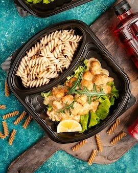 Bovenaanzicht dieet pasta met kip en een schijfje citroen met een rucola